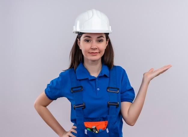 Zelfverzekerd jonge bouwer meisje met witte veiligheidshelm en blauw uniform houdt hand omhoog en legt hand op taille op geïsoleerde witte achtergrond met kopie ruimte