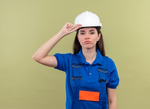 Zelfverzekerd jonge bouwer meisje met witte veiligheidshelm en blauw uniform houdt hemlet en kijkt naar de camera op geïsoleerde groene achtergrond