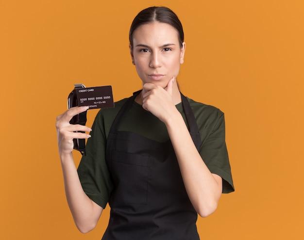 Zelfverzekerd jonge brunette kapper meisje in uniform legt hand op kin met tondeuses en creditcard geïsoleerd op oranje muur met kopie ruimte