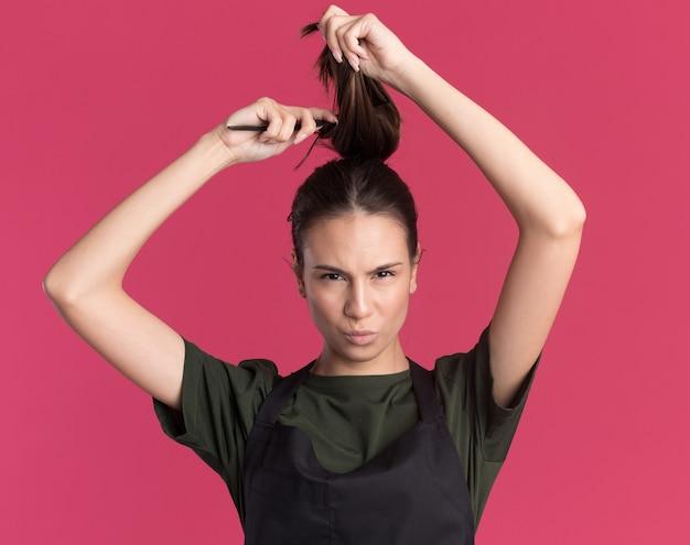 Zelfverzekerd jonge brunette kapper meisje in uniform liften haar en kam op roze