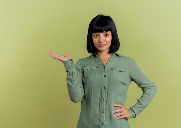 Zelfverzekerd jonge brunette kaukasisch meisje legt hand op taille en houdt hand open kijken naar camera geïsoleerd op olijfgroene achtergrond met kopie ruimte