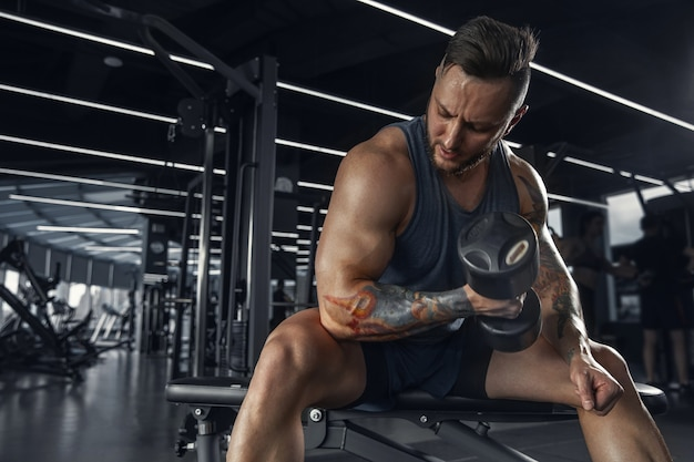 Zelfverzekerd. jonge gespierde blanke atleet oefenen in de sportschool met de gewichten. mannelijk model dat krachtoefeningen doet, zijn bovenlichaam traint. wellness, gezonde levensstijl, bodybuilding concept.