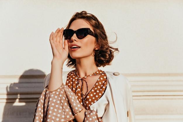 Zelfverzekerd kaukasisch meisje dat in donkere zonnebril in afstand kijkt. buiten schot van goedgehumeurde modieuze vrouw.