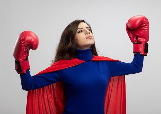 Zelfverzekerd kaukasisch superheld meisje met rode cape dragen bokshandschoenen staat met verhoogd