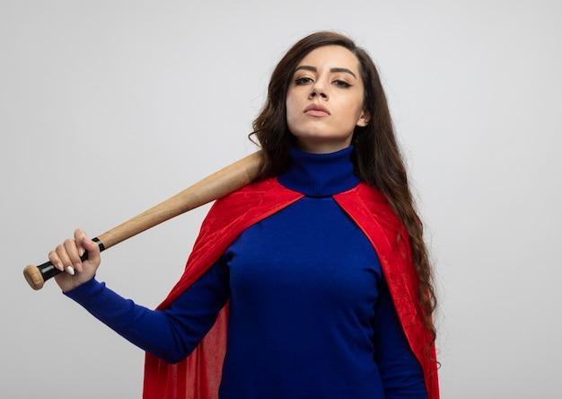 Zelfverzekerd kaukasisch superheld meisje met rode cape houdt honkbalknuppel op schouder op wit