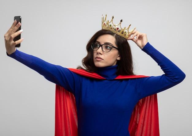 Zelfverzekerd kaukasisch superheld meisje met rode cape in optische bril houdt kroon boven het hoofd en kijkt