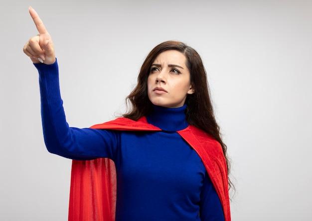 Zelfverzekerd kaukasisch superheld meisje met rode cape kijkt en wijst op wit