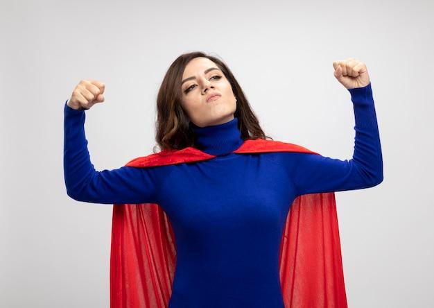 Zelfverzekerd kaukasisch superheld meisje met rode cape spanningen biceps en kijkt naar kant op wit
