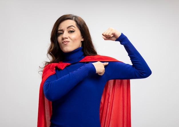 Zelfverzekerd kaukasisch superheld meisje met rode cape tijden en punten op biceps op wit