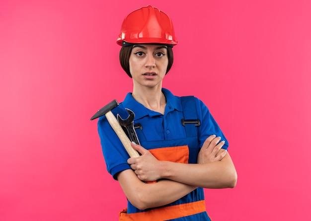 Zelfverzekerd kijkend naar de camera van een jonge bouwvrouw in uniform die een hamer vasthoudt met een steeksleutel die de handen kruist