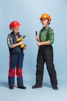 Zelfverzekerd. kinderen dromen over beroep van ingenieur. jeugd, planning, onderwijs en droomconcept. succesvolle medewerker worden in de maakindustrie, bouwnijverheid, infrastructuur.