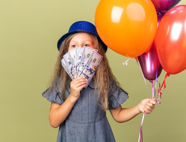 Zelfverzekerd klein blond meisje met blauwe feestmuts met helium ballonnen en geld voor haar gezicht geïsoleerd op olijfgroene muur met kopie ruimte