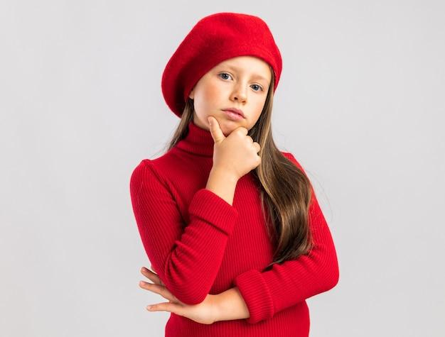 Zelfverzekerd klein blond meisje met een rode baret die de hand op de kin houdt en naar de voorkant kijkt geïsoleerd op een witte muur met kopieerruimte