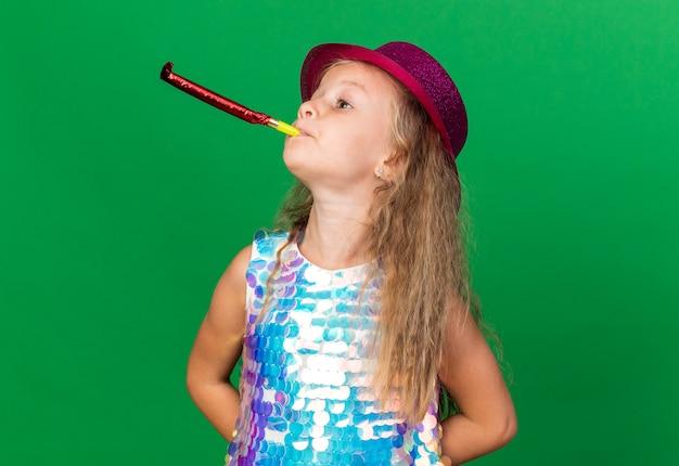 Zelfverzekerd klein blond meisje met paarse feestmuts die feestfluitje blaast en kijkt naar kant geïsoleerd op groene muur met kopieerruimte