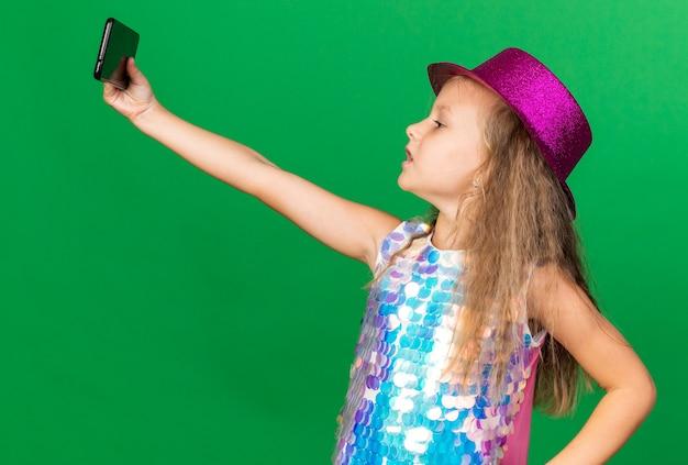 Zelfverzekerd klein blond meisje met paarse feestmuts die selfie neemt op telefoon geïsoleerd op groene muur met kopieerruimte