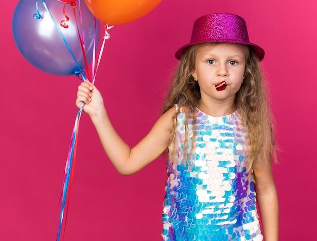 Zelfverzekerd klein blond meisje met paarse feestmuts met helium ballonnen en blazen partij fluitje geïsoleerd op roze muur met kopie ruimte