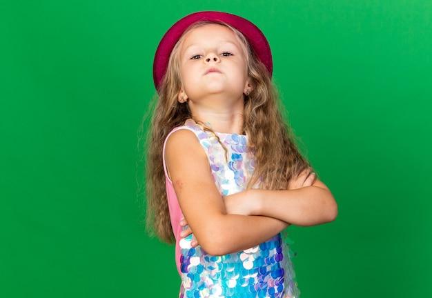 Zelfverzekerd klein blond meisje met paarse feestmuts permanent zijwaarts met gekruiste armen geïsoleerd op groene muur met kopie ruimte