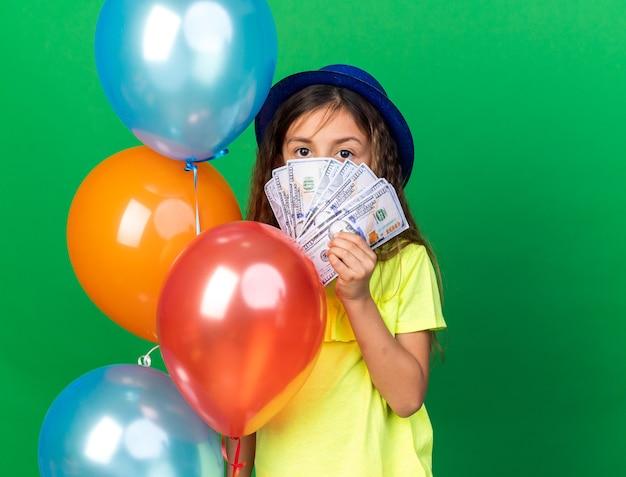 Zelfverzekerd klein kaukasisch meisje met blauwe feestmuts met helium ballonnen en geld geïsoleerd op groene muur met kopie ruimte