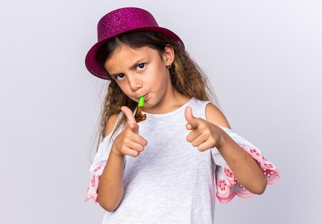 Zelfverzekerd klein kaukasisch meisje met paarse feestmuts die feestfluit blaast en wijst geïsoleerd op een witte muur met kopieerruimte