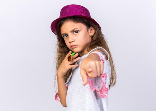 Zelfverzekerd klein kaukasisch meisje met paarse feestmuts partij fluitje houden en wijzen geïsoleerd op een witte muur met kopie ruimte