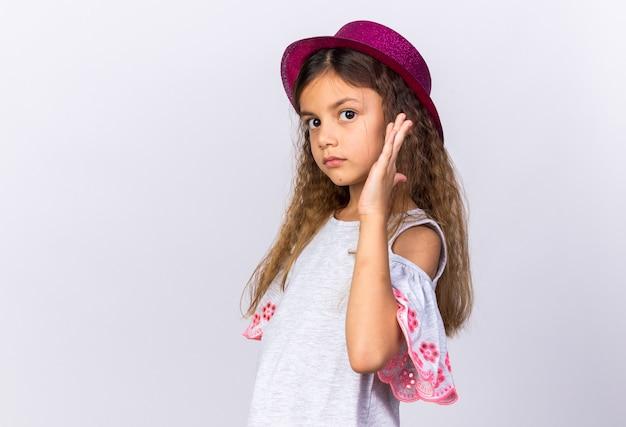 Zelfverzekerd klein kaukasisch meisje met paarse feestmuts staande met opgeheven hand geïsoleerd op een witte muur met kopieerruimte