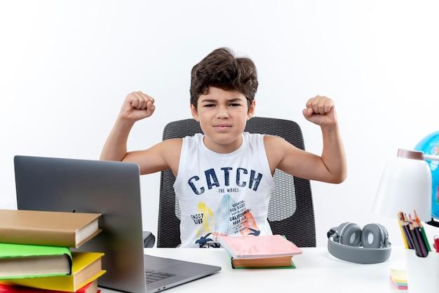 Zelfverzekerd kleine schooljongen zittend aan een bureau met hulpmiddelen van de school doen sterk gebaar geïsoleerd op een witte achtergrond