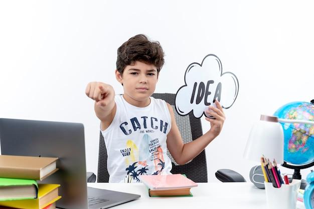 Zelfverzekerd kleine schooljongen zittend aan een bureau met schoolhulpmiddelen idee zeepbel houden en tonen je gebaar geïsoleerd op een witte achtergrond