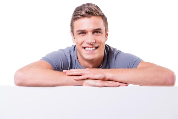 Zelfverzekerd knap. knappe jonge man die naar de camera kijkt en glimlacht terwijl hij zijn armen gekruist houdt en naar de kopieerruimte leunt