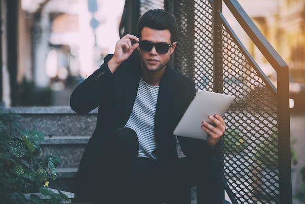 Zelfverzekerd knap. knappe jongeman in slimme vrijetijdskleding die een digitale tablet draagt en zijn zonnebril aanpast terwijl hij buiten op de trap zit