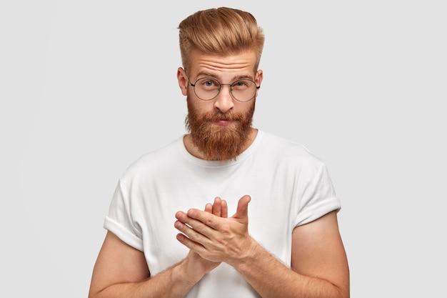 Zelfverzekerd knappe man applaudisseert als iemand begroet, heeft een dikke gemberbaard en trendy kapsel, nonchalant gekleed, klapt in beide handen, geïsoleerd over witte muur. mensen en felicitatie concept
