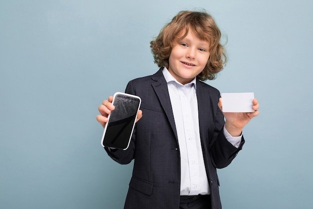 Zelfverzekerd knappe positieve gelukkige jongen met krullend haar die de telefoon en de creditcard van de kostuumholding dragen