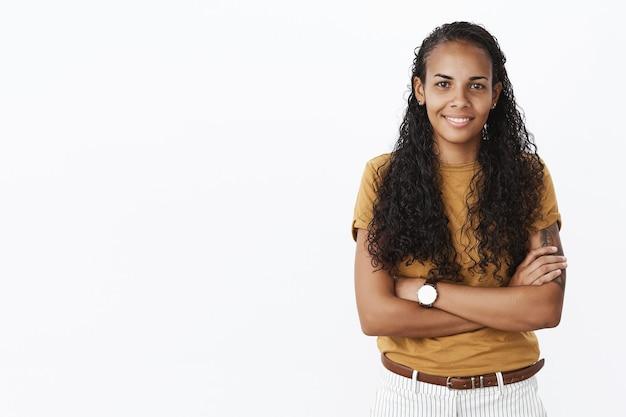Zelfverzekerd lachende jonge afro-amerikaanse vrouw met gekruiste armen op zoek bepaald