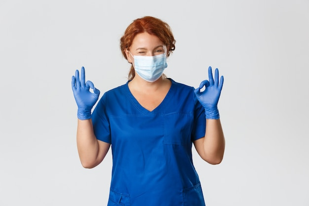 Zelfverzekerd lachende roodharige arts, vrouwelijke verpleegster in medisch masker, handschoenen, oke gebaar tonen, garanderen veilige en kwaliteitscontrole bij kliniek