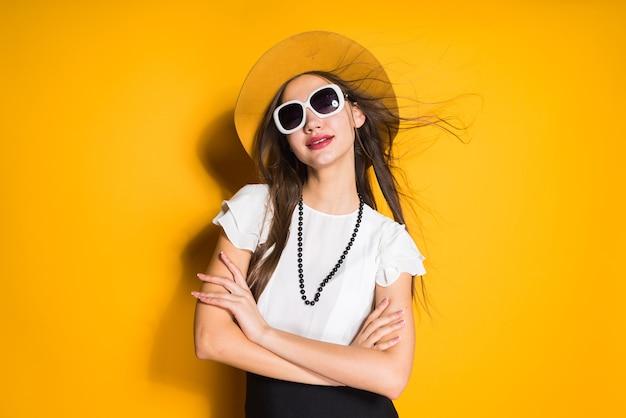 Zelfverzekerd langharig meisjesmodel in hoed en zonnebril die zich voordeed op gele achtergrond