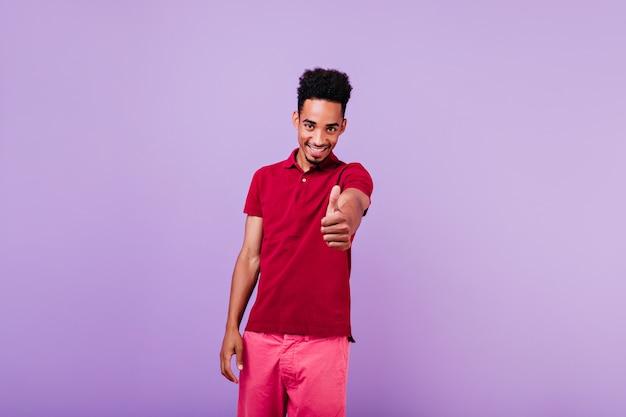 Zelfverzekerd mannelijk model in lichte kleren die duim tonen. lachen blij afrikaanse man staan