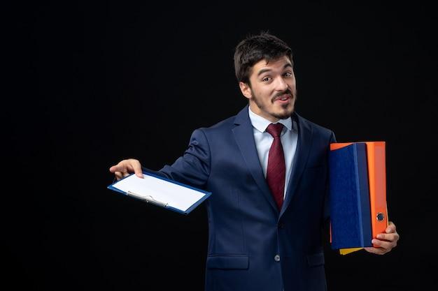 Zelfverzekerd mannetje in pak dat verschillende documenten vasthoudt en iets vraagt op een geïsoleerde donkere muur