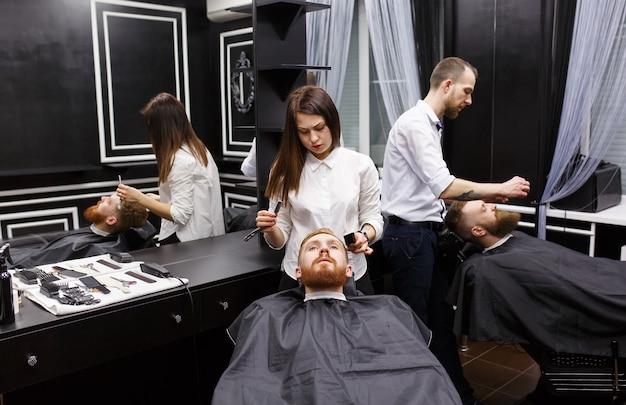 Zelfverzekerd mans bezoekende haarstylisten in kapperszaak.