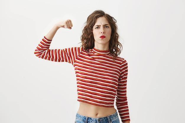 Zelfverzekerd meisje buigt biceps, pronkt met spieren na de sportschool