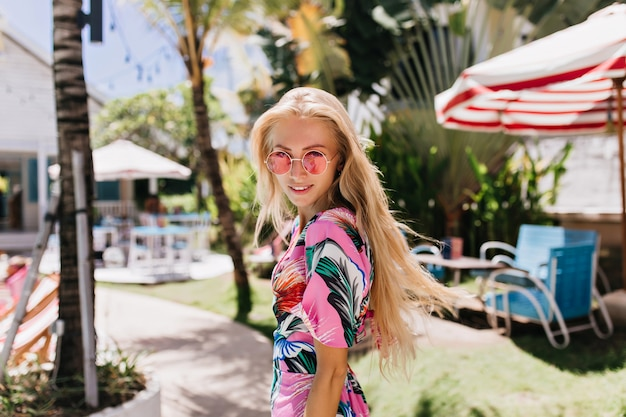 Zelfverzekerd meisje dat in de zomerkleren over schouder met mooie glimlach kijkt.