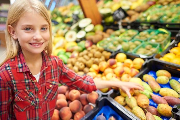 Zelfverzekerd meisje dat rijp fruit kiest