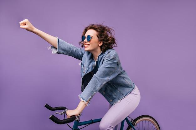 Zelfverzekerd meisje in spijkerjasje rijden op de fiets en zwaaiende hand. indoor foto van geïnspireerde jonge dame in glazen zittend op de fiets.