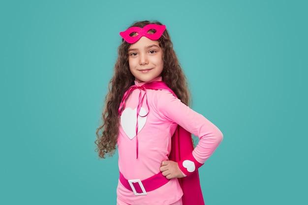 Zelfverzekerd meisje in superheld kleren camera kijken