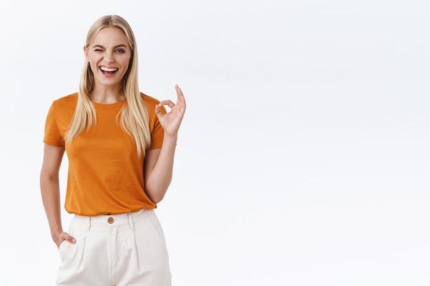 Zelfverzekerd meisje kreeg alles onder controle. ongehinderde knappe moderne blonde vrouw in oranje t-shirt, met tatoeages, oke bevestigingsgebaar tonen, sluw en koket knipogen, tevreden glimlachend