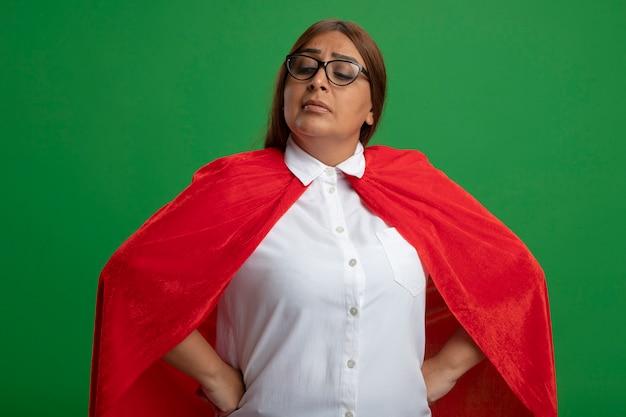 Zelfverzekerd middelbare leeftijd superheld vrouw met bril neerkijkt handen op heup geïsoleerd op groene achtergrond