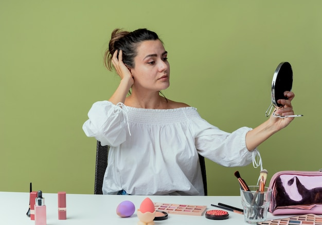 Zelfverzekerd mooi meisje zit aan tafel met make-up tools hand op hoofd houdt en kijkt naar spiegel geïsoleerd op groene muur