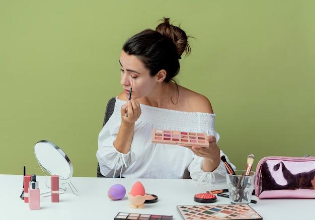 Zelfverzekerd mooi meisje zit met gesloten ogen aan tafel met make-up tools kijkt naar spiegel houden oogschaduw palet en oogschaduw toe te passen met make-up borstel geïsoleerd op groene muur