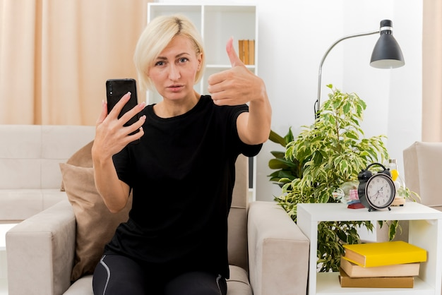 Zelfverzekerd mooie blonde russische vrouw zit op fauteuil duimen omhoog houden telefoon