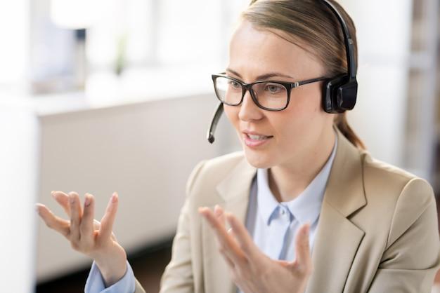 Zelfverzekerd mooie jonge vrouwelijke manager in hoofdtelefoon praten via videoconferenties en gebaren handen tijdens het uitleggen van informatie aan de klant