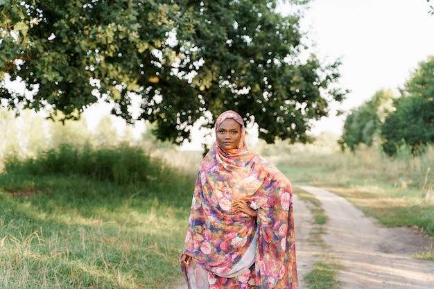 Zelfverzekerd moslim zwart meisje weared in hijab glimlacht in de buurt van groene boom