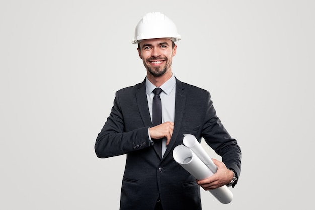 Zelfverzekerd positieve mannelijke bouwontwikkelaar in elegante formele pak en bouwvakker met papieren ontwerpen in de hand op zoek